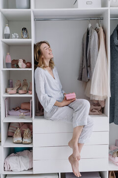 Young woman sits in a modern dressing room with a gift box. Girl dreams of something
