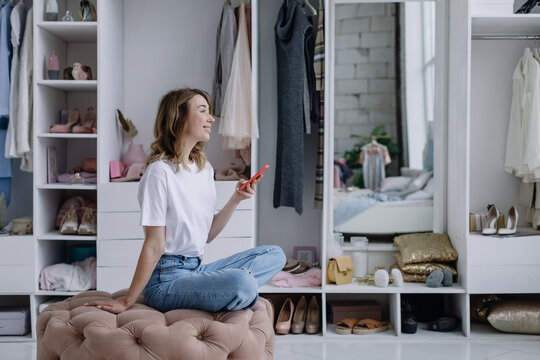 Young woman sits in a modern dressing room with a phone. Girl dreams of something