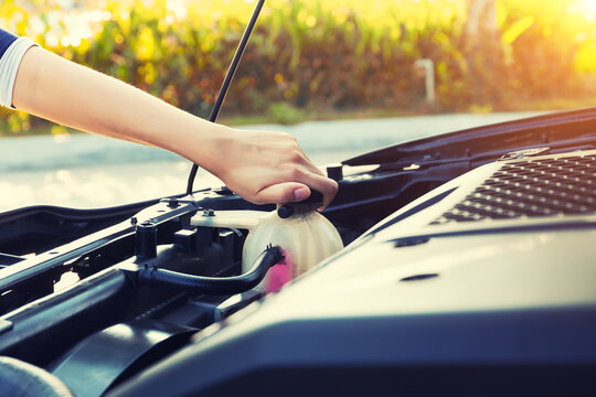 Check auto car's coolant level. That service, repair or maintenance by women hand to open cap of tank or reservoir for filling liquid cooled engine with water, antifreeze in radiator, cooling system.