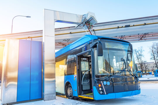 High-voltage electric charging station for charging electric buses at the final stop of the city route. Bus at the final stop with an open door.