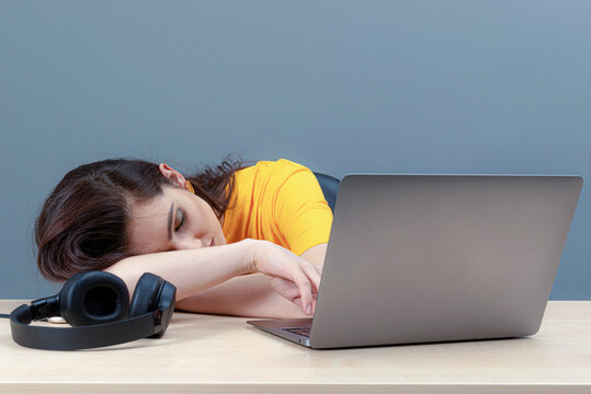 young female student sleeping near laptop during learning at home, distance online education