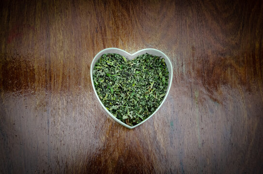chopped cannabis herb in a heart on wood