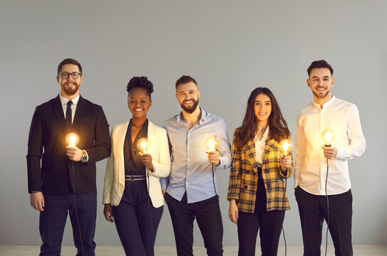 Teamwork and brainstorming, innovation idea creation and share. Diverse interracial business team positive smiling holding glowing light idea bulb standing over grey copy space studio background