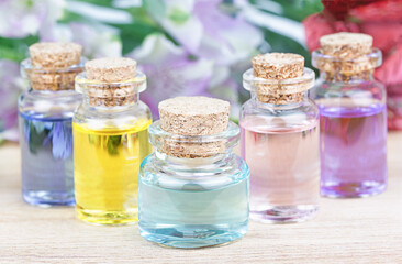 Set of colorful bottles with floral essential oil.