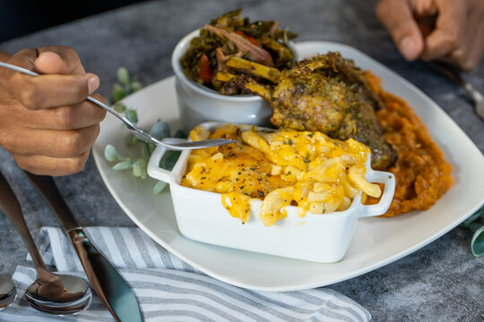 Black hands eating southern cooked soul food