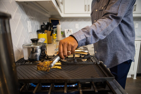 African American man cooking dinner for family at home