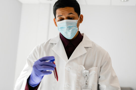 Latino medical professional in a mask analyzing blood sample