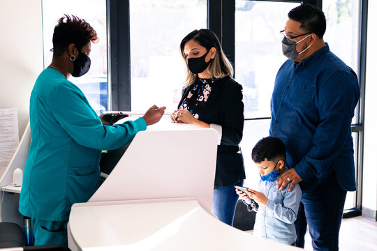 Black nurse reviewing medical forms with Latino family at doctor office