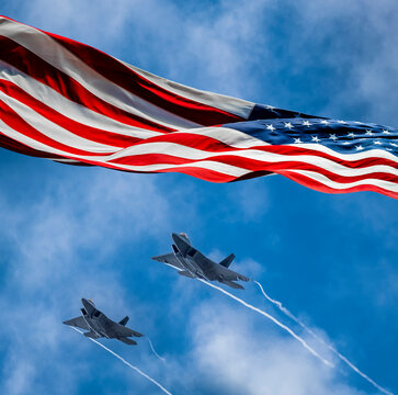 American flag blowing in wind and Lockheed Martin F-22 Raptors flying against sky