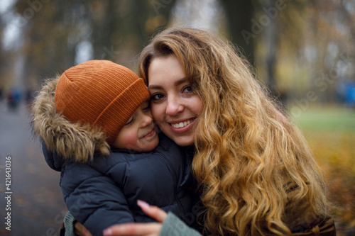 portrait of a young woman who smiles and hugs a child in warm clothes. young mother. mother's day and motherhood. younger brother and older sister