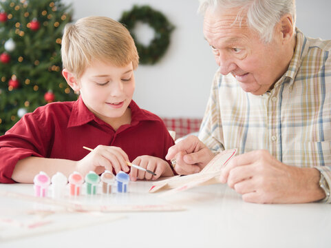 Grandfather and grandson (8-9 years) painting model airplane