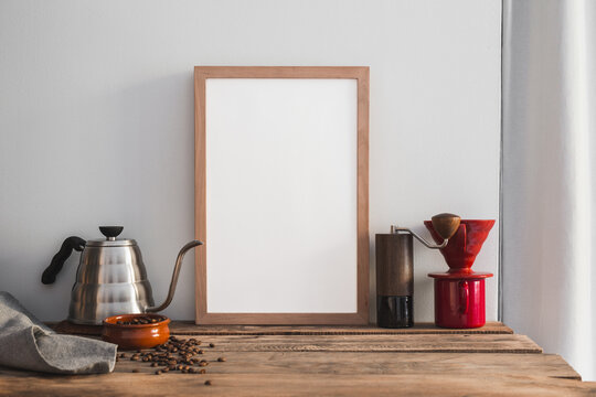 Mock- up frame and home barista brewing set with drip kettle, manual grinder and coffee beans.