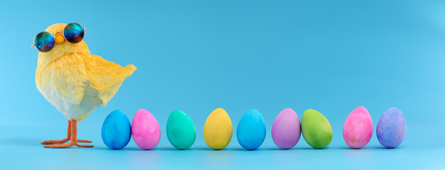 Easter decoration of a yellow chick wearing silly sunglasses with a row of colorful painted Easter eggs.