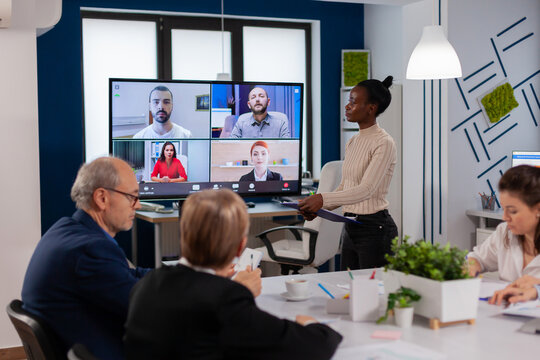 African woman discussing with remote managers on video call presenting new partners on webcam. Business people talking to webcam, do online conference participate internet brainstorming, distance