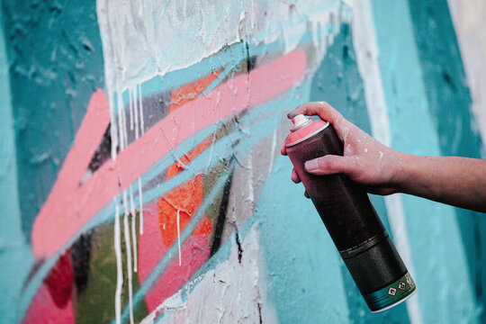Closeup shot of an artist's hand holding a paint spray can for drawing graffiti on the wall