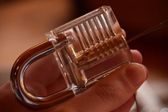 Close-up Of Human Hand On Pick Lock