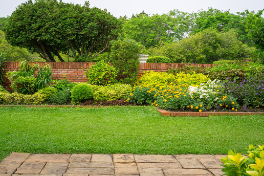 Backyard English cottage garden on brown pavement and green lawn