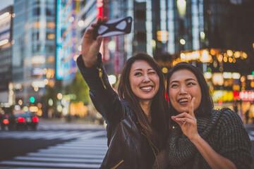 Two japanese women around in Tokyo during daytime. Making shopping and having fun