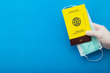 Hand holding vaccine passports as proof that the holder has been vaccinated against Covid-19,...