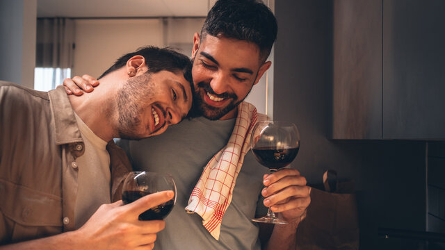 Happy Gay Couple in Love Drink Wine, Chat, Embrace and Hug. One Puts his Hed on a Shoulder. Two Boyfriends Have Lovely Romantic Evening. Partners Talk, Share Beautiful Moments. Close-up Portrait