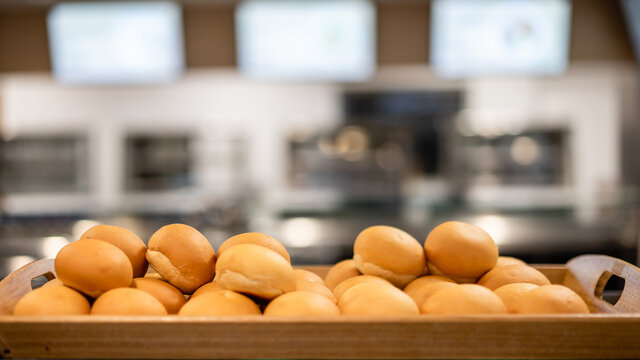 A lot of ready-made fresh bread in a bakery with blurred bakery shop in wholesale store with baking machine, selective focus . Bread making business.