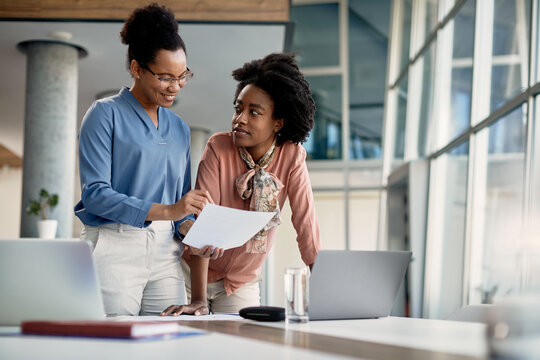 Black business mentor feeling satisfied with reports of her assistant who works at company office.