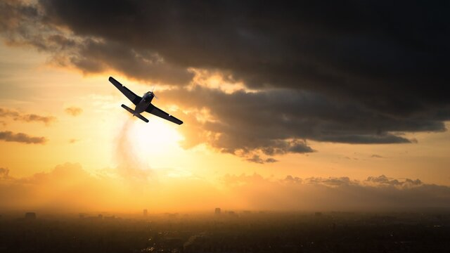 Silhouette of a World War II aircraft flying at sunset, USA