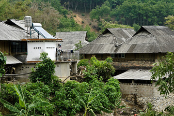 Fototapeta Tin-roofed houses (one with a water tank and solar panel) in a Jinuo ethnic minority village, Xishuangbanna, Yunnan Province, China obraz