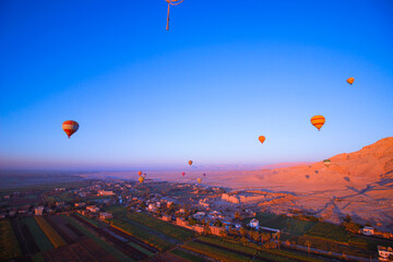 Fototapeta Hot Balloons Floating Over The West Bank In Luxor. Over The Valley Of Kings