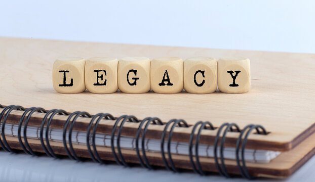 word LEGACY made with letters on wooden blocks on wooden notepad