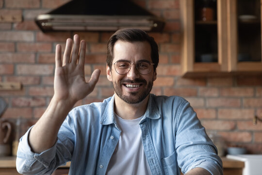 Close up screen view of smiling millennial man in glasses wave greet talking on video call on computer. Happy young Caucasian guy have webcam digital online conference at home. Virtual event concept.