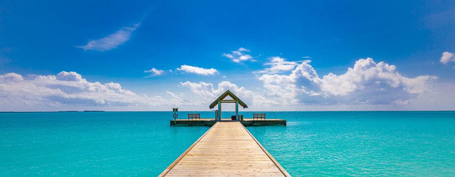 Tropical pier to paradise island beach. Amazing ocean lagoon, sea horizon under blue sky. Idyllic, meditation, inspiration scenery. Wellbeing, relaxation, positive thinking. Travel, summer wellness
