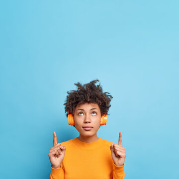 Vertical image of serious beautiful Afro American woman concentrated above indicates upwards shows copy space for your advertising content or logo listens music via headphones. Place your text here