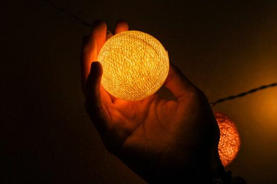 Close-up Of Hand Holding Illuminated Orange