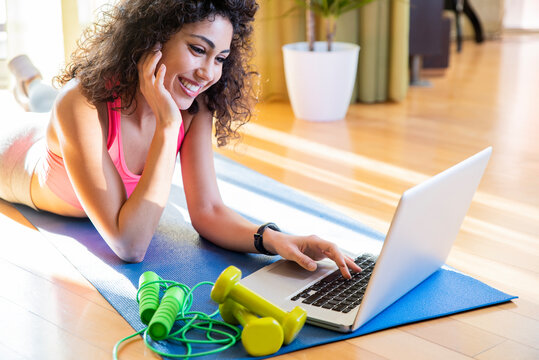 Sporty woman in sportswear is sitting on the floor with dumbbells using a pc laptop in the living room - Young girl training fitness at home - Sport and technology concept.