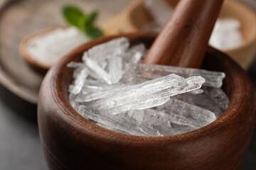Fototapeta Menthol crystals in wooden mortar, closeup view obraz