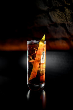view of illuminated transparent glass with cold drink with zest standing on bar counter