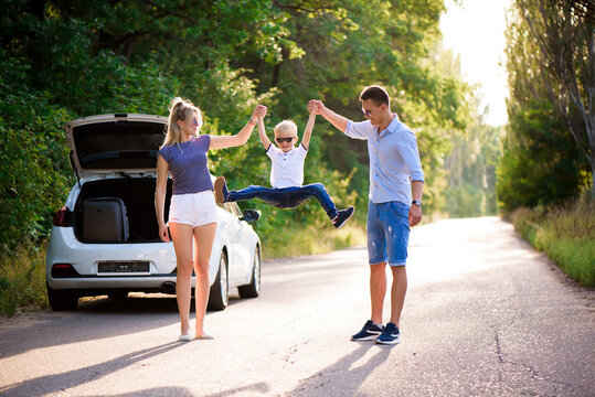 Young family travels by car. Dad, mom and son take a break from driving a car and walk.