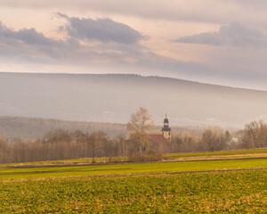 Wieża kościelna w dolinie na tle góry.
