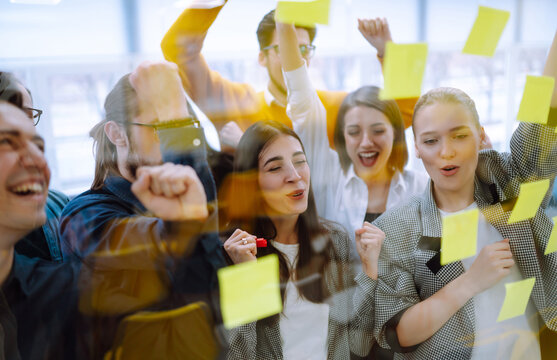 Young business team people brainstorm on corporate project together write strategy tasks on post in sticky notes stand behind glass wall, diverse staff group planning management concept.