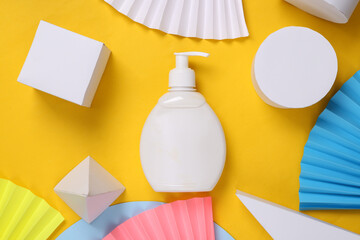 Cream bottle on yellow abstract background with geometric shapes. Minimalism. Concept art. Creative...