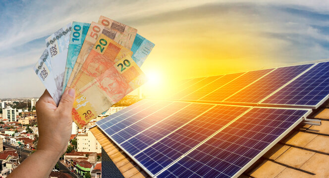 Solar Energy Economy, holding Brazilian money in front of the photovoltaic panel on a roof, sunset background.