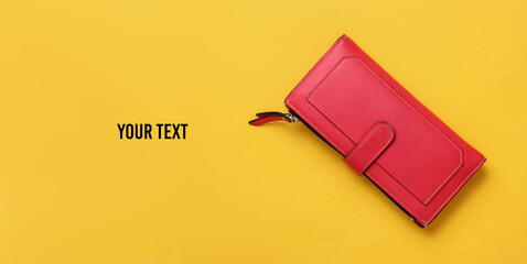 Red leather wallet on yellow background. Top view. Copy space
