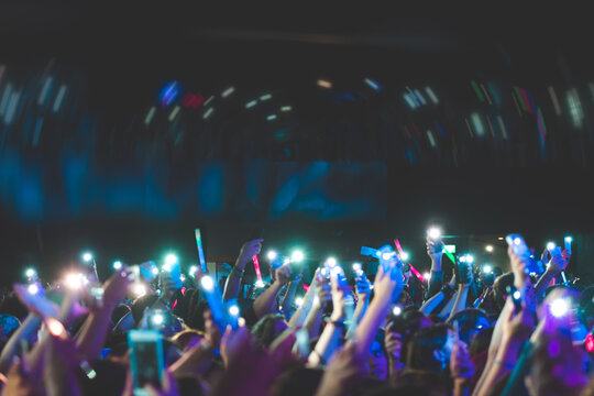 Large Group Of Crowd Cheering By Flashing Lights At Music Concert