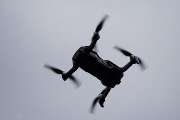 Fototapeta Dron szpiegujący na niebie, obracające sie śmigła. Czarny dron na niebie. Elektryczny ptak na niebie.  obraz