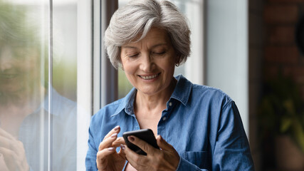 Smart aged user. Smiling active retired hispanic woman enjoy playing game in phone application get...