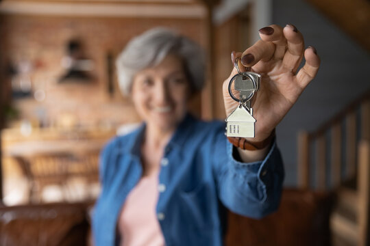 House of dream. Blurred portrait of happy elderly female of senior age becoming landlord homeowner pose in modern country cottage hold bunch of keys celebrate moving day. Focus on key in old lady hand