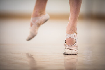 Legs and slippers of classical ballet dancers rehearsing