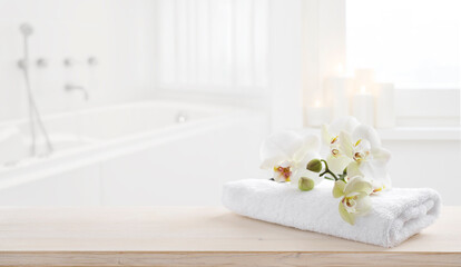 Towel and orchid flowers on wooden table with copy space