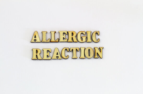 Allergic reaction written with wooden letters on white background